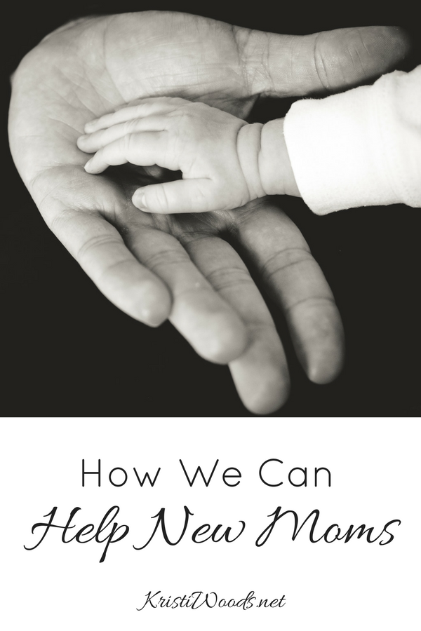 Adult hand outreached and an infant hand on it. Christian blog post title underneath: How can we Help New Moms?