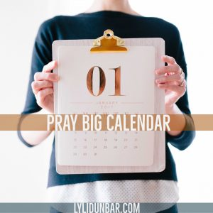 "woman holding a calendar with the words ""Pray Big Calendar"" in front"